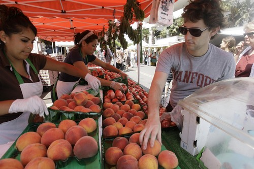 Alex Kendall, right, buys peaches from Griselda Martinez, left and Leanah Velazquez at the farmer's market Wednesday July 16, 2008 in Santa Monica, Calif. Food prices showed a big increase in June, rising by 0.7 percent, more than double the 0.3 percent increase of May. Vegetable prices shot up by 6.1 percent, the biggest increase in nearly three years. (AP Photo/Nick Ut)
