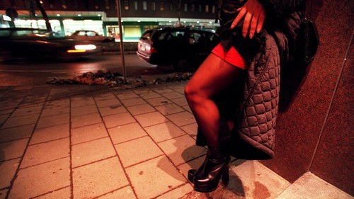 A prostitute waits for business on the street