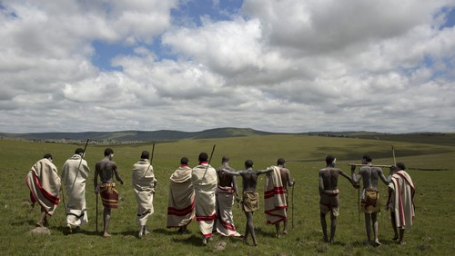 "Initiates pose as they walk on a field in Qunu, in the Eastern Cape December 15, 2013. Every year, thousands of youths leave their parents to spend weeks in the care of traditional leaders at an initiation school where they are circumcised, a rite of passage commonly referred to as ""Ukwaluka"" or ""going to the mountain""."