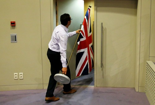 An official carries a Union Jack flag ahead of a news conference by Britain's Secretary of State for Exiting the European Union Davis and EU's chief Brexit negotiator Barnier in Brussels