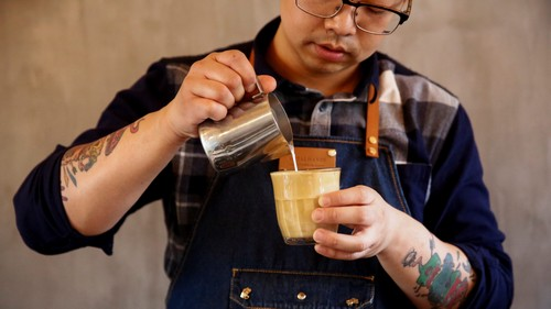 A barista pours milk into coffee at the Metal Hands cafe in Beijing, China May 3, 2017.