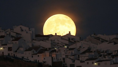 The Supermoon rises over houses in Olvera, in the southern Spanish province of Cadiz, July 12, 2014. Occurring when a full moon or new moon coincides with the closest approach the moon makes to the Earth, the Supermoon results in a larger-than-usual appearance of the lunar disk.