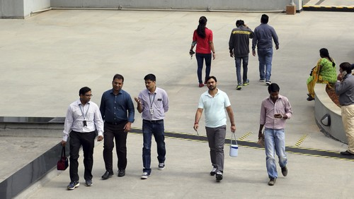 FILE- In this Jan. 18, 2016 file photo, Wipro Ltd. employees walk inside the company's compound during a break at their headquarters in Bangalore, India. The shares of top Indian IT companies are falling in response to news of proposed U.S. legislation that would require salaries for H-1B visa holders to be doubled to make it harder for companies to replace American workers with those from countries like India. (AP Photo/Aijaz Rahi, File)