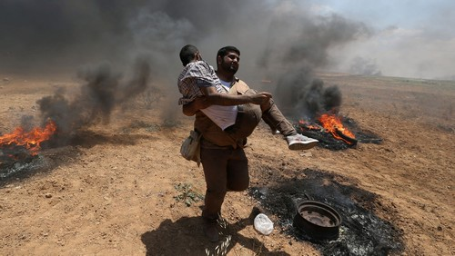 A wounded Palestinian demonstrator is evacuated during a protest against U.S. embassy move to Jerusalem and ahead of the 70th anniversary of Nakba, at the Israel-Gaza border in the southern Gaza Strip May 14, 2018. REUTERS/Ibraheem Abu Mustafa - RC1119F74020