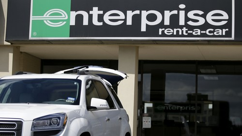 A vehicle with its' rear tailgate opened sits parked in front of a Enterprise Rent-A-Carl location, Wednesday, Oct. 2, 2013, in Dallas. Enterprise Holdings, the nation's largest rental car company, plans to add more than 11,000 new full-time jobs by mid-2014. (AP Photo/Tony Gutierrez)