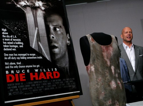 """Actor Bruce Willis poses beside a movie poster and shirt from the movie """"Die Hard"""" which he donated to the Smithsonian's National Museum of American History in Washington"""