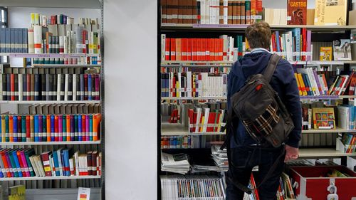 A man looks at books in Goethe Institute's library in Barcelona February 1, 2013. Barcelona's Goethe Institute offers more than 170 German courses every year. In the last two years they have seen the number of students grow by 75 percent, most of them people under 25 who want to seek a better future in Germany, according to the centre director, Marion Haase. Picture taken February 1, 2013. REUTERS/Albert Gea (SPAIN - Tags: BUSINESS EMPLOYMENT EDUCATION) - GM1E9250K5W01